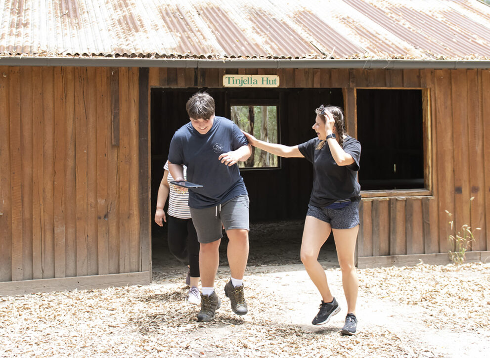 Carer and person exploring outside a barn near Kuitpo