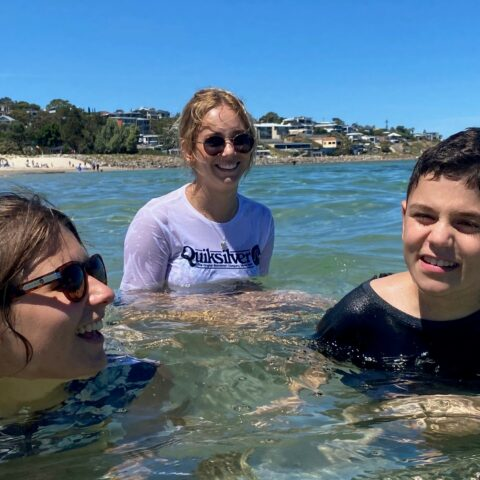 Volunteers with disabled child in the ocean